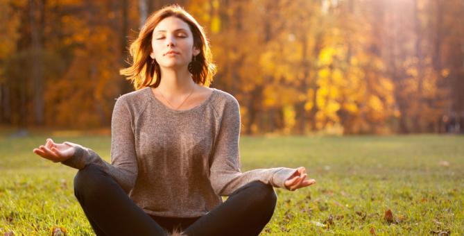 dívka, která medituje v podzimní krajině